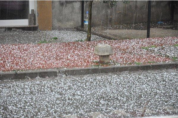 Dolu yağışı sokakları beyaza bürüdü